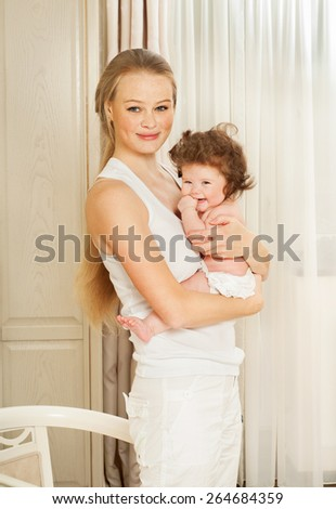 Mother and baby playing and smiling in home interior. Happy family.