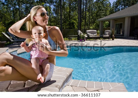 Mother and baby playing by swimming pool - stock photo