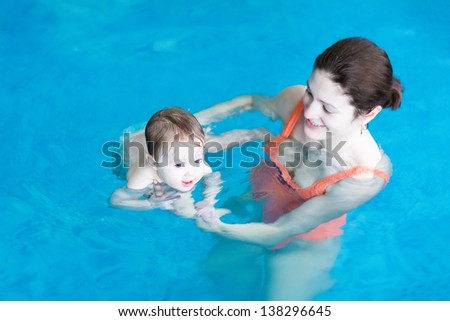 Mother and baby playing in a swimming pool - stock photo