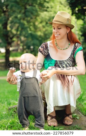 Mother and baby playing in the park. The first steps - stock photo