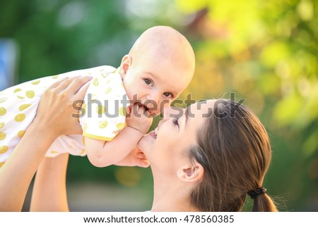 Mother and baby playing on street