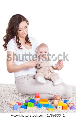 mother and baby playing with building blocks toy over white