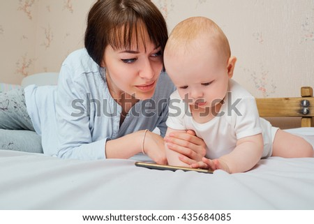 Mother and baby playing with phone on the bed. Mother is looking at baby. - stock photo
