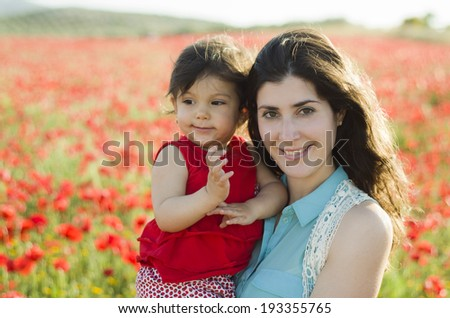 Mother and baby posing in outdoors  poppies field - stock photo