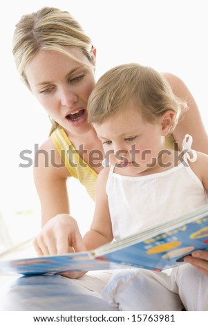 Mother and baby reading book indoors and pointing - stock photo