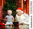 mother and baby sitting next christmas tree - stock photo