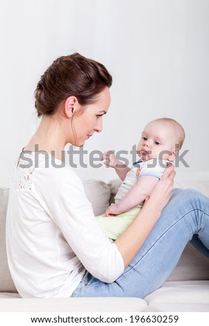 Mother and baby sitting on a sofa - stock photo