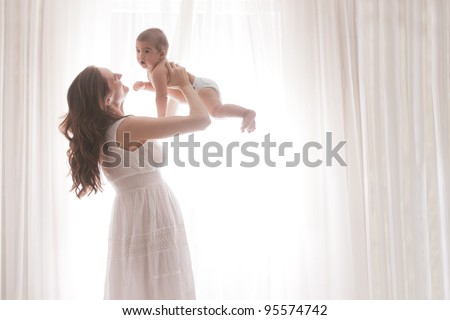 Mother and Baby Son Against White Curtains