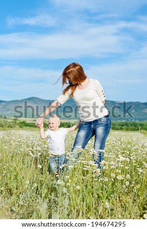 mother and baby son are playing in field