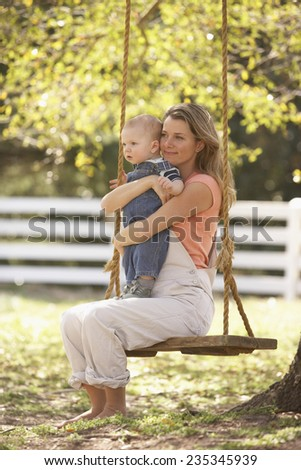 Mother and Baby Son on Rope Swing - stock photo