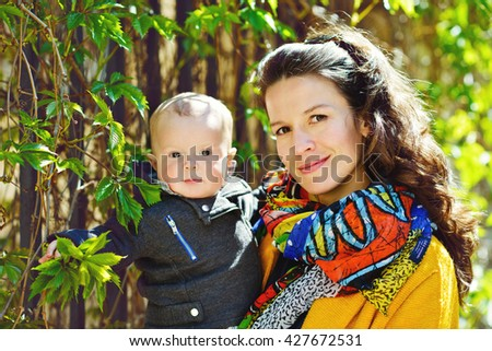 mother and baby son outdoors, focus on mother's face - stock photo