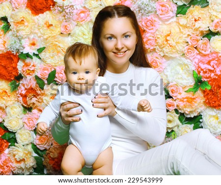 Mother and baby together against colorful flowers - stock photo