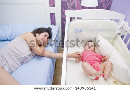 Mother and baby together in the bedroom. Holding hands.