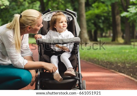 Mother and baby walking and enjoying nature, blonde young woman with a child