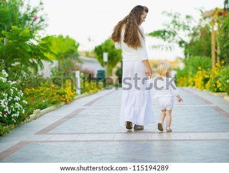 Mother and baby walking outdoors. Rear view - stock photo