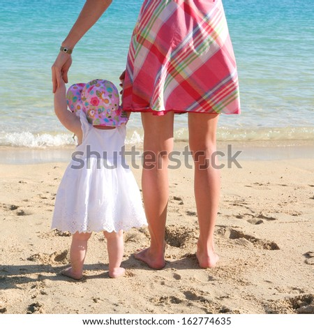 Mother and baby: young woman is teaching her sweet toddler daughter to walk her first steps on a sandy tropical beach