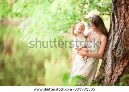 mother and beautiful woman in long dress is standing in the park or forest near the trees and holding her smiling  little baby girl daughter saing hello on her hands hugging her