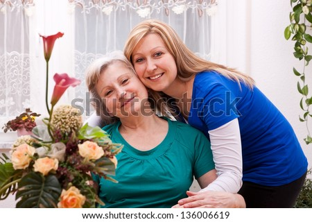 Mother and blond daughter in living room - stock photo