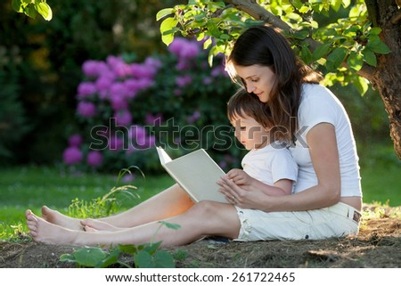 Mother and boy, reading a book, summertime in a garden, beautiful sunset light - stock photo