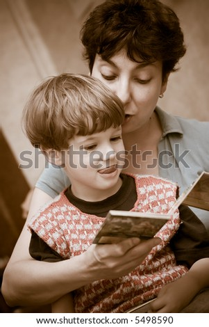 Mother and  boy together read the book of fairy tales before a dream - stock photo