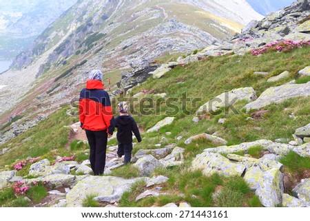 Mother and boy walking across narrow mountain trail - stock photo