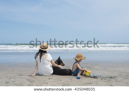 Mother and child and Doberman relax on the beach