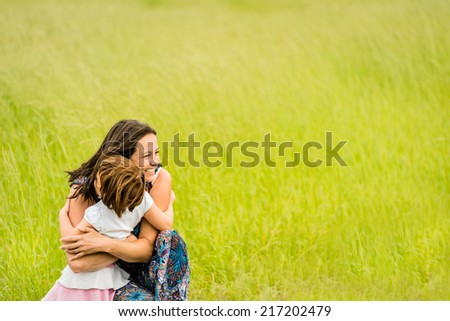 Mother and child are hugging and embracing outdoor in nature