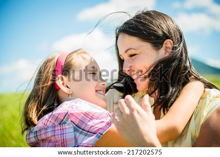 Mother and child are hugging and having fun outdoor in nature - stock photo