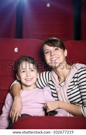 Mother and child are watching a movie at the cinema - stock photo