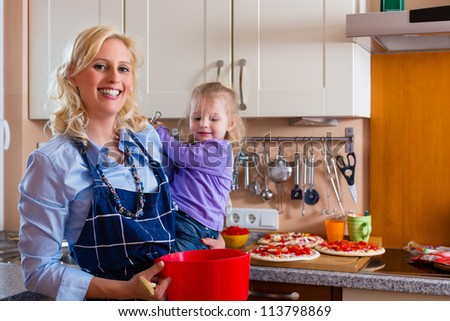 Mother and child baking pizza in their kitchen, the daughter is a baby child