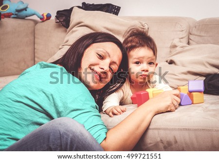 Mother and child by a couch with toy blocks