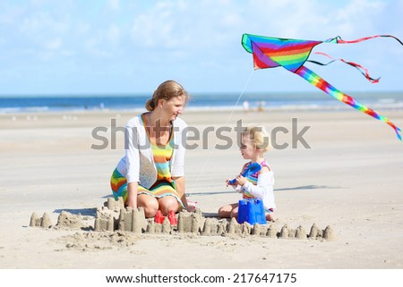 Mother and child concept: young beautiful woman and her lovely cute toddler daughter playing together on the beach building sand castles and flying colorful kite at the sea - stock photo