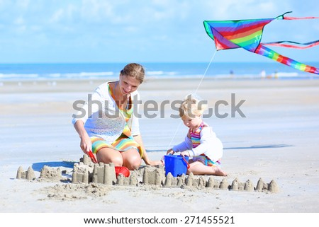 Mother and child concept: young beautiful woman and her lovely cute toddler daughter playing together with toys on the beach building sand castles and flying colorful kite, North Sea, Belgian coast - stock photo