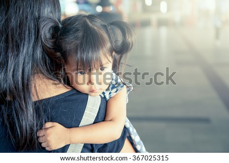 Mother and child,cute little girl resting on her mother's shoulder in the train station, vintage filter effect,selective focus - stock photo