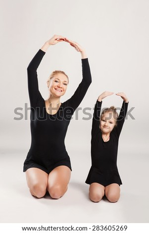 Mother and child daughter make fitness exercises - stock photo