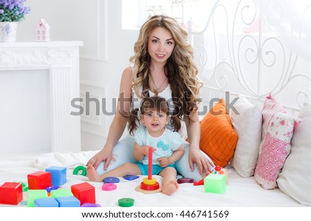 Mother and child daughter playing together, build from the constructor. cute mother and her son play together indoor. Young mom with her child play together