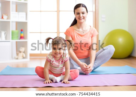 Mother and child daughter practicing yoga together in living room at home. Sport and family concept