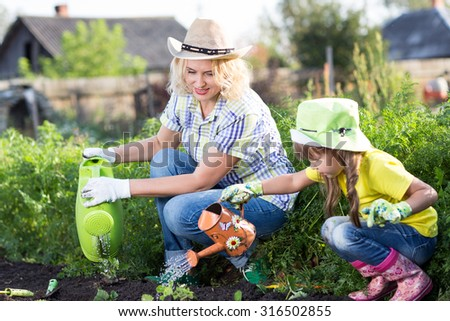 Mother and child daughter working in the garden - stock photo