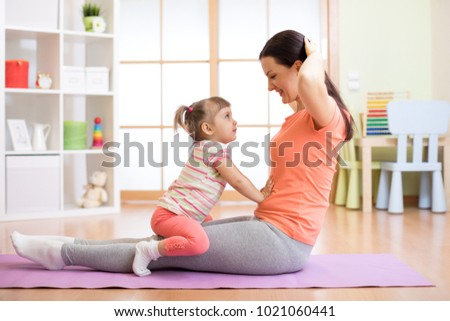 Mother and child doing fitness exercises on mat at home