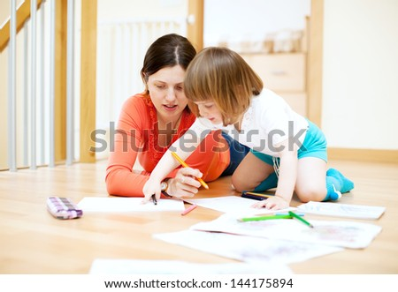 mother and  child drawing on paper at parquet floor. Focus on woman only