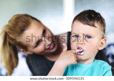 Mother and child eating a cake / desert with their fingers and enjoying themselves - stock photo