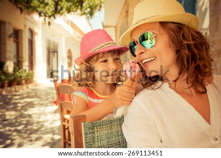 Mother and child eating ice cream in summer cafe outdoors - stock photo