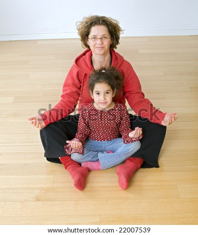 mother and child exercising together on floor