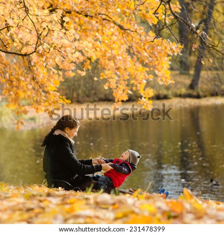 Mother and child having fun in autumn - stock photo
