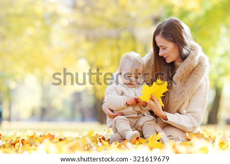 Mother and child having fun in autumn park among yellow leaves - stock photo