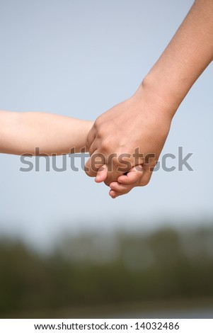 mother and child holding hands closeup on sky background