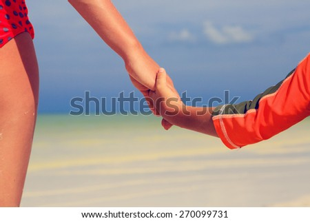 mother and child holding hands on sea summer beach - stock photo