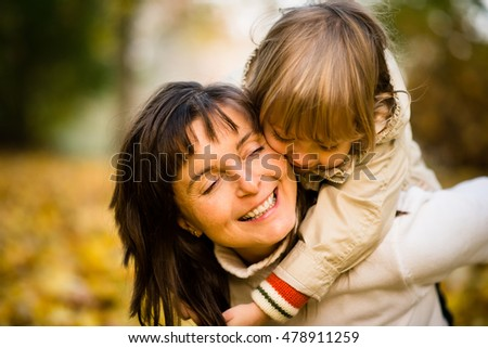 Mother and child hugging in nature - girl is embracing her around neck