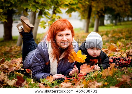 mother and child in autumn forest in warm weather. The concept of motherhood