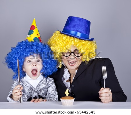 Mother and child in funny wigs and cake at birthday. Studio shot. - stock photo